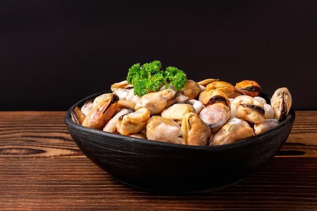 Bevroren schelpdierenvlees met groene peterselie in een zwarte kleikom op houten tafel.