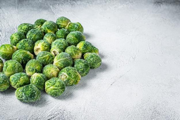 Bevroren spruitjes groene kool op keukentafel. witte achtergrond. bovenaanzicht. ruimte kopiëren.