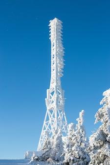 Bevroren televisie of cellulaire toren in zware sneeuw dichtbij skicentrum. telecommunicatietorens met schotel en mobiele antenne tegen blauwe hemel in de winterbergen.