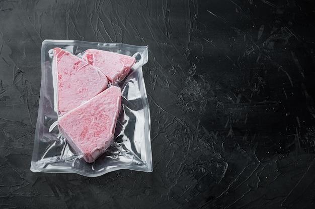 Bevroren tonijnsteak vacuümverpakkingsset, op zwarte stenen achtergrond, met copyspace en ruimte voor tekst