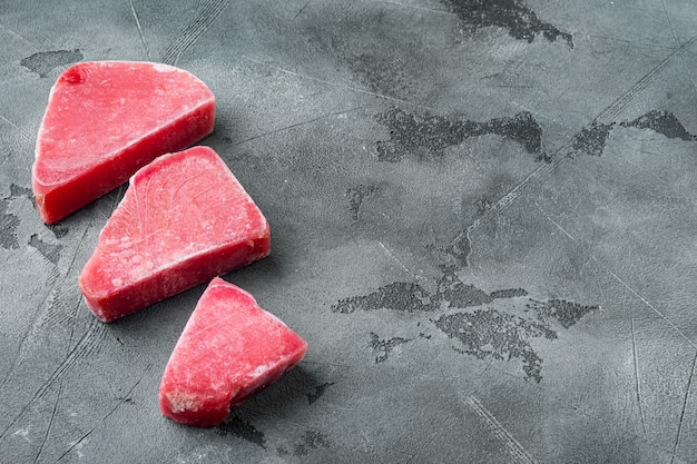 Bevroren tonijnsteaks set, op grijze stenen achtergrond, met copyspace en ruimte voor tekst