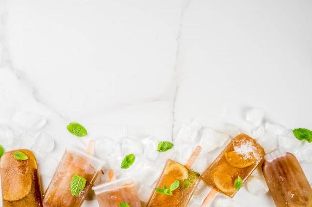 Bevroren verfrissende drankjes zomer cocktail ijslollys recept cuba libre koude zoete thee of koffie met ijs limoen en muntblaadjes op