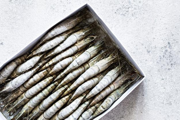 Bevroren verse garnalen in een doos op een grijze achtergrond