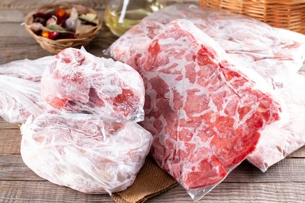 Bevroren vlees in een plastic zak op een houten tafel. diepvries voedsel.