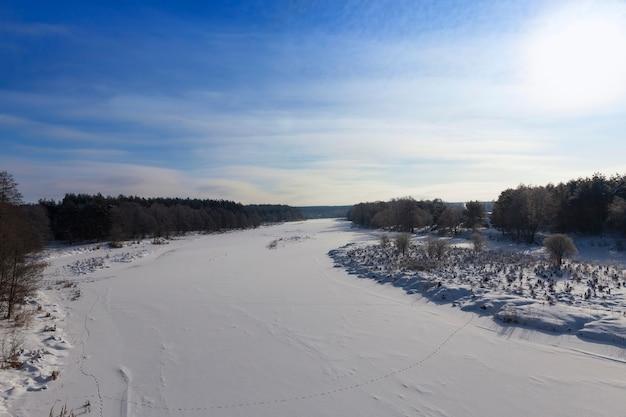 Bevroren water in de rivier tijdens koud weer, winterseizoen met vorst en sneeuw