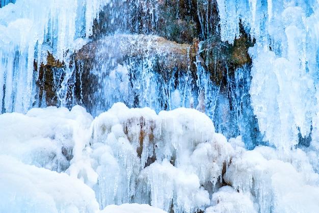Bevroren waterval van blauwe ijspegels op de rots
