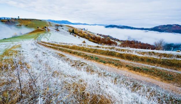 Bevroren weg bedekt met witte vorst tegen de achtergrond van een prachtige blauwe lucht en pluizige witte mist