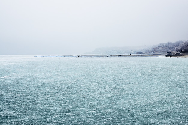 Bevroren zee en pier in de verte