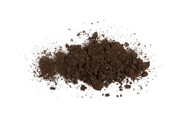 Bevruchte droge vuilgrond geïsoleerd. gedroogde grondstapel, mestgrond, dor vuil, natuurlijke zwarte vuile aardetextuur op witte bovenaanzicht als achtergrond