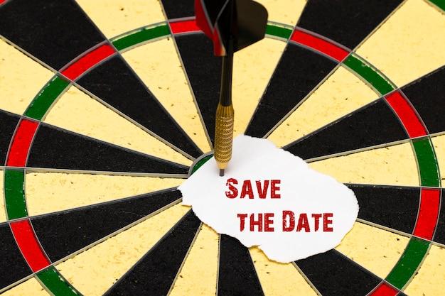 Bewaar de datum. darten met dartpijl die op een vel papier was gespeld voor labels