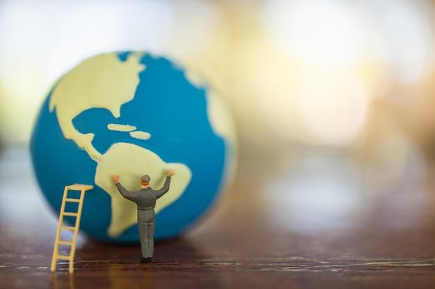 Bewaar global environment care concept. sluit omhoog van arbeiders miniatuurmensen met ladder die miniwereldbal op witte lijst met exemplaarruimte schoonmaken.