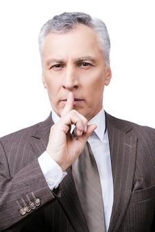 Bewaar mijn geheim! ernstige volwassen man in formalwear die de vinger op de lippen houdt en naar de camera kijkt terwijl hij tegen een witte achtergrond staat