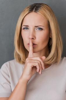 Bewaar mijn geheim! ernstige volwassen vrouw die vinger op de lippen houdt en naar de camera kijkt