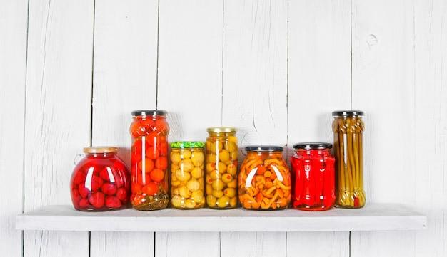 Bewaard voedsel in glazen potten, op houten plank. diverse gemarineerde gerechten