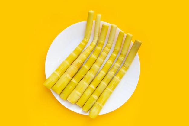 Bewaarde bamboescheuten in witte plaat op gele achtergrond.