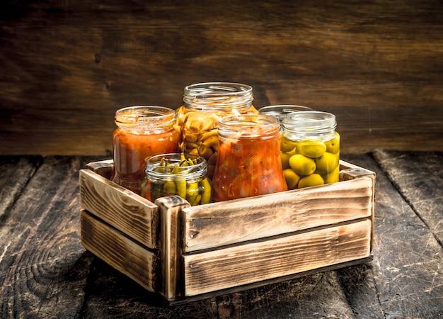 Bewaart champignons en groenten in een doos. op een houten tafel.