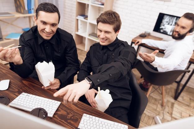 Bewakers op het werk glimlachen en kijken naar de monitor.
