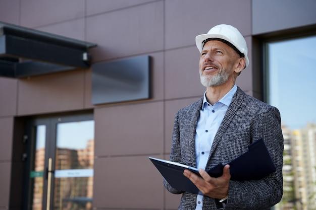 Bewaking van het proces zelfverzekerde architect-ingenieur-manager van middelbare leeftijd die een helm draagt en wegkijkt