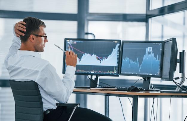 Bewakingsinformatie. jonge zakenman in formele kleding is op kantoor met meerdere schermen. conceptie van uitwisseling en geld.