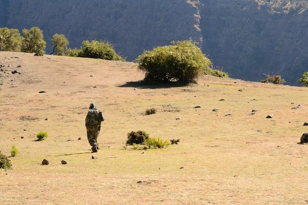 Bewapende boswachter die in het nationale park simien mountain in het droge seizoen, de reisbestemming van ethiopië lopen