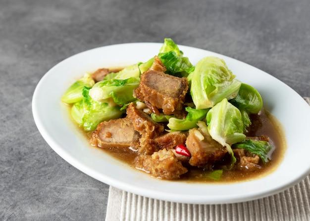Beweeg fried baby cabbage met knapperig varkensvlees op plaat, aziatisch voedsel