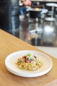 Beweeg gebraden chinese noedel met ham en krabvlees op houten lijst met onduidelijk beeldachtergrond.