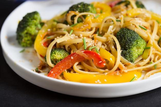 Beweeg gebraden gerecht chinese noedels met groenten op de zwarte die achtergrond, in wok wordt gekookt, omhoog sluit