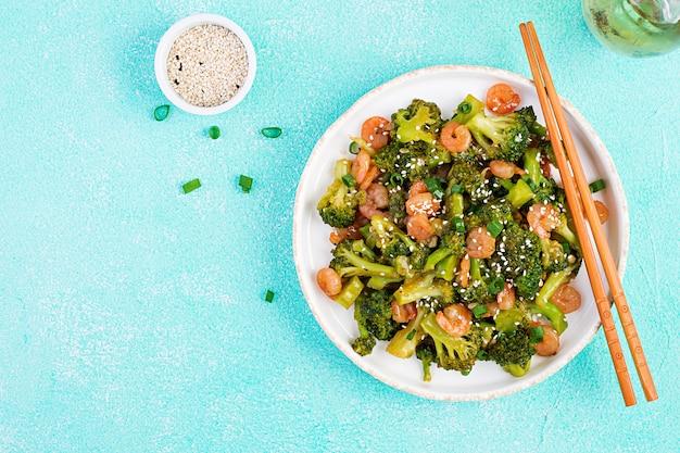Beweeg gebraden gerechtgarnalen met broccoli dicht omhoog op een plaat. garnalen en broccoli. bovenaanzicht, overhead