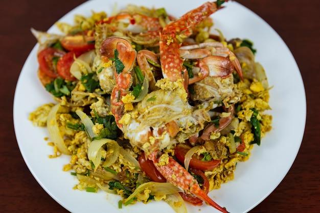 Beweeg gebraden krab met kerriepoeder, close-up, thais voedsel op een houten achtergrond
