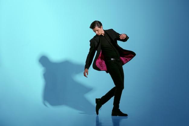 Bewegend beeld van een aantrekkelijke sterke jonge man in volledig elegant zwart pak, geïsoleerd op een blauwe achtergrond. horizontale weergave.