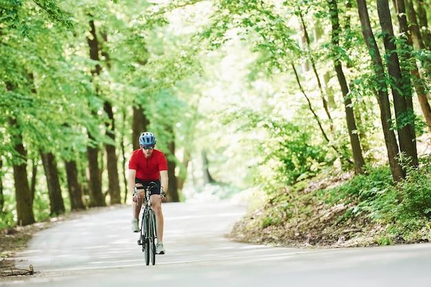 Bewegende activiteit. fietser op een fiets is op de asfaltweg in het bos op zonnige dag
