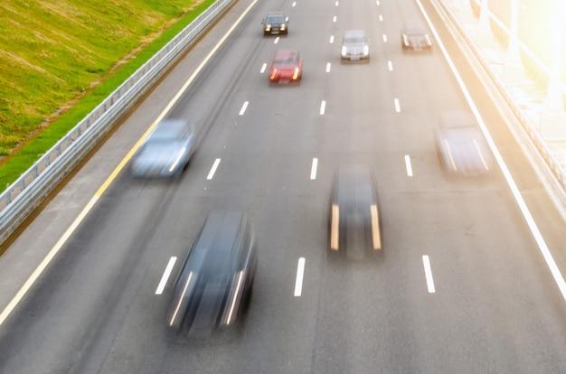 Bewegende auto's op een meerbaanswegasfalt laten de markeringen los bewegende auto's op een meerbaanswegasfalt laten de markeringen los.