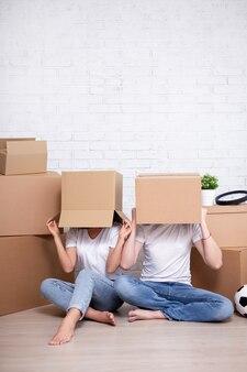 Bewegende dag - jong stel bedekt hun gezicht met kartonnen dozen en kopieert ruimte over witte bakstenen muurachtergrond