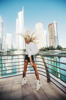 Bewegende fotografie van een russische dame in de stad met een hoog gebouw in een geweldige stedelijke levensstijl van de stad in het golfland van de emiraten.