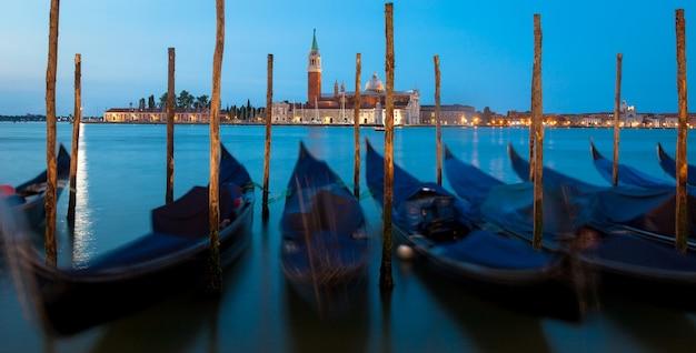 Bewegende gondels aan de waterkant van venetië, san giorgio maggiore op de achtergrond