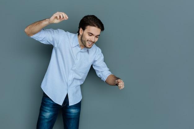 Beweging is leven. vrolijke gelukkig aardige man glimlacht en beweegt zijn handen terwijl je naar beneden kijkt