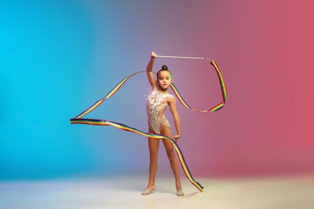Beweging. klein kaukasisch meisje, ritmische turnerstraining, geïsoleerd presteren