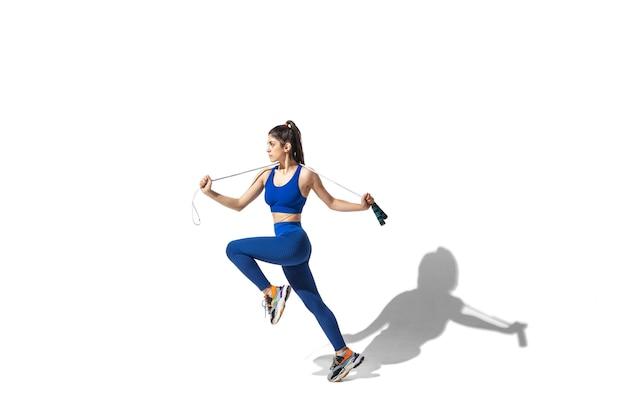Beweging. mooie jonge vrouwelijke atleet oefenen op witte studio achtergrond, portret met schaduwen. sportief fit model in beweging en actie. lichaamsbouw, gezonde levensstijl, stijlconcept.