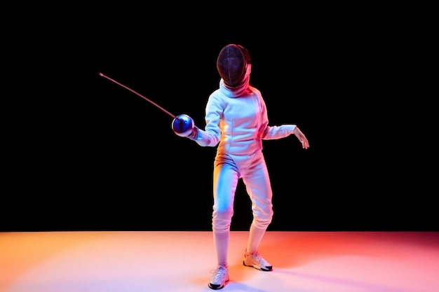 Beweging. tienermeisje in hekwerkkostuum met in hand zwaard geïsoleerd op zwarte achtergrond, neonlicht. jong model oefenen en trainen in beweging, actie. copyspace. sport, jeugd, gezonde levensstijl.