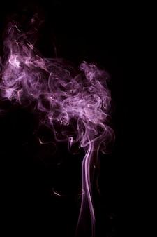 Beweging van roze rook die op zwarte achtergrond wordt uitgespreid