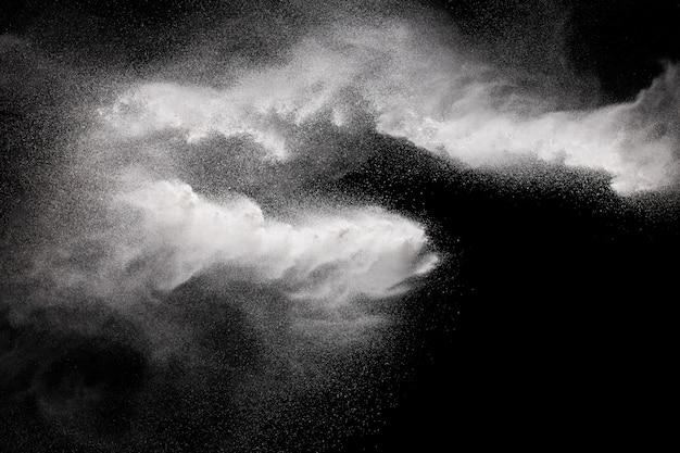 Bewegingsexplosie van wit poeder op een zwarte achtergrond bevriezen.