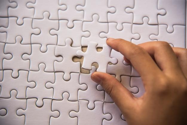 Bewerk een paar witte puzzels die op het punt staan te vallen om een compleet werkblad te krijgen