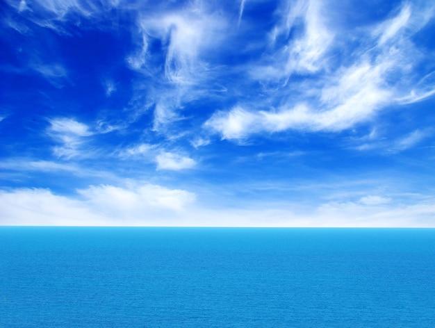 Bewolkt blauwe lucht boven een oppervlak van de zee