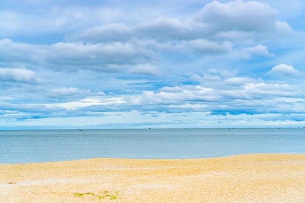 Bewolkte blauwe hemel en zee met gouden zandstrand.