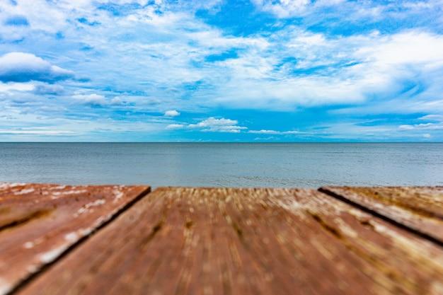 Bewolkte blauwe hemel en zee met houten planken
