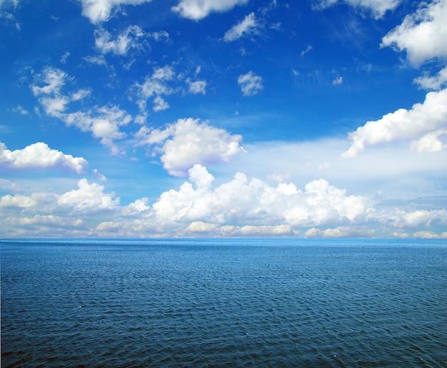 Bewolkte blauwe lucht boven een oppervlak van de zee