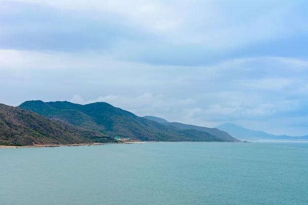 Bewolkte dag, zand verlaten strand van de kust in de buurt van het standbeeld van de godin nanshan in de zuid-chinese zee. sanya, eiland hainan, china. natuur landschap.