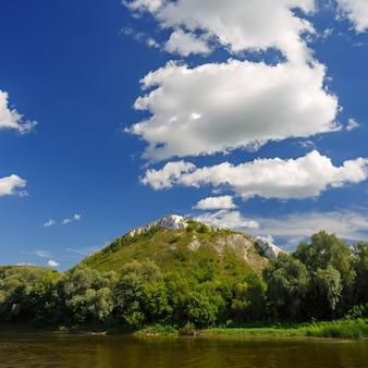 Bewolkte hemel boven de rivier bij de berg