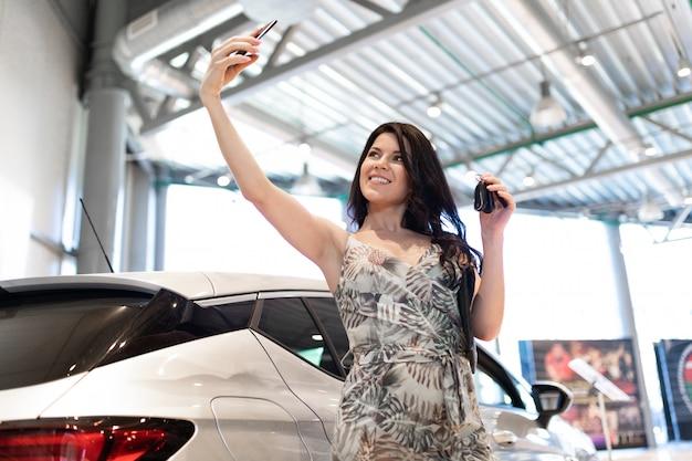 Bewonderenswaardige brunet maakt een selfie en bezit in de buurt van haar nieuwe auto in de showroom van de dealer