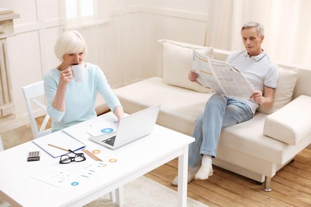 Bewonderenswaardige, productieve intelligente familie die tijd doorbrengt in de woonkamer terwijl de dame werkt aan een analyse van zakelijke gegevens en haar man een krant leest